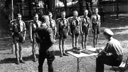 Jungen in Uniform stehen vor zwei Soldaten stramm.
