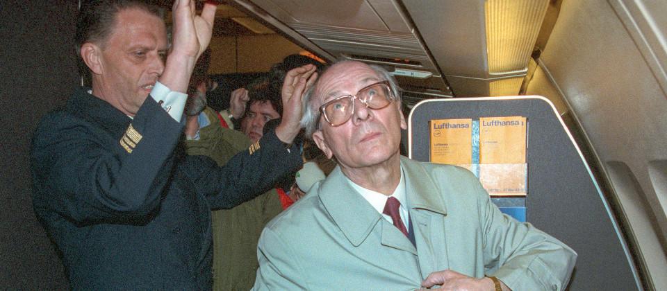 Erich Honecker in Mantel mit Hut im Flugzeug.