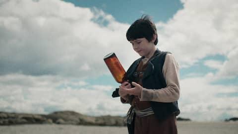 Ein Junge findet eine Flaschenpost
