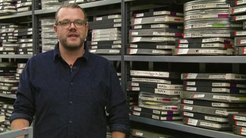 Sönke Treu vom Fernseharchiv des NDR erläutert das Projekt NDR Retro vor einem Regal mit Filmrollen