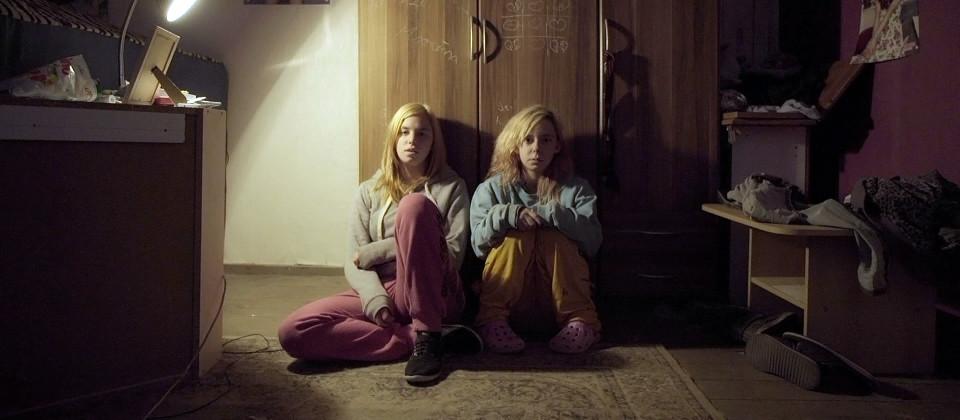 Zwei Mädchen sitzen vor einem Schrank.