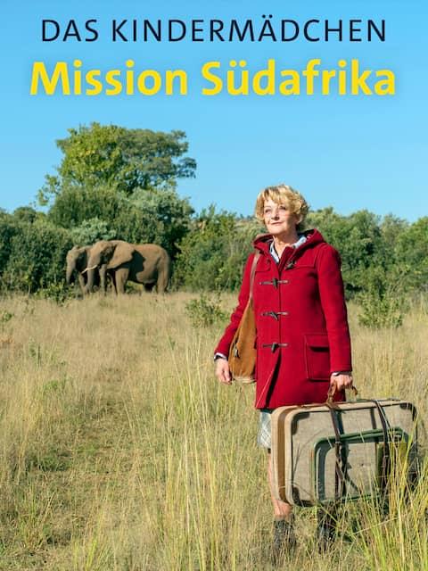 Eine Frau steht mit einem Koffer in der Hand in der Steppe in Südafrika. Im Hintergrund stehen Elefanten.