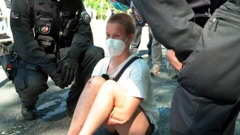 Aktivistin umringt von Polizist:innen bei einer Straßenblockade.