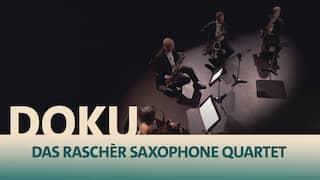 Das Raschèr Saxophone Quartet von oben aufgenommen in einem Lichtkegel erhellt und einem halben Stuhlkreis in einem schwarzen Raum
