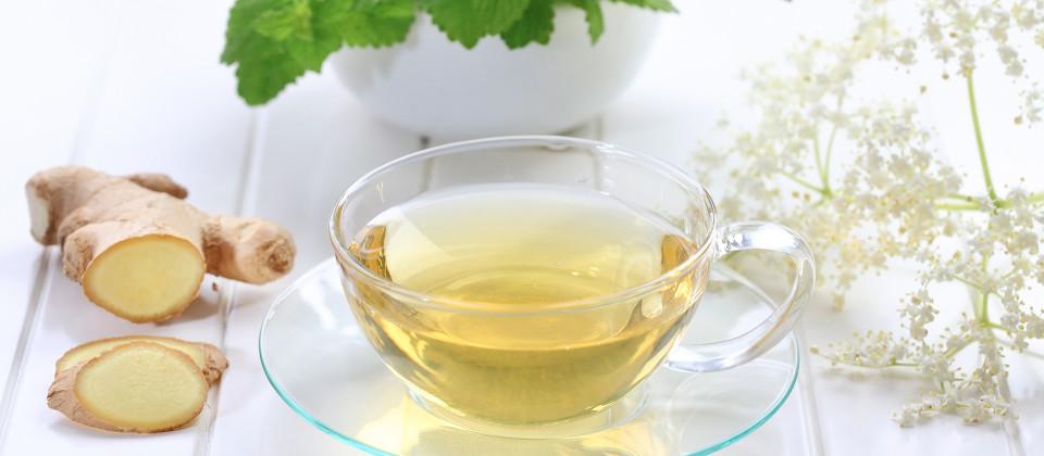 Eine Tasse mit Tee, Ingwer daneben und Minzblätter.