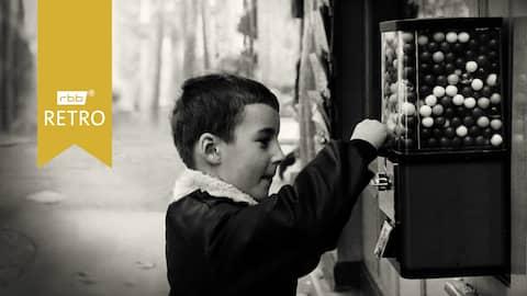 Kleiner Junge steht vor einem Bonbonautomaten (Quelle: rbb/imago images/KHARBINE-TAPABOR)