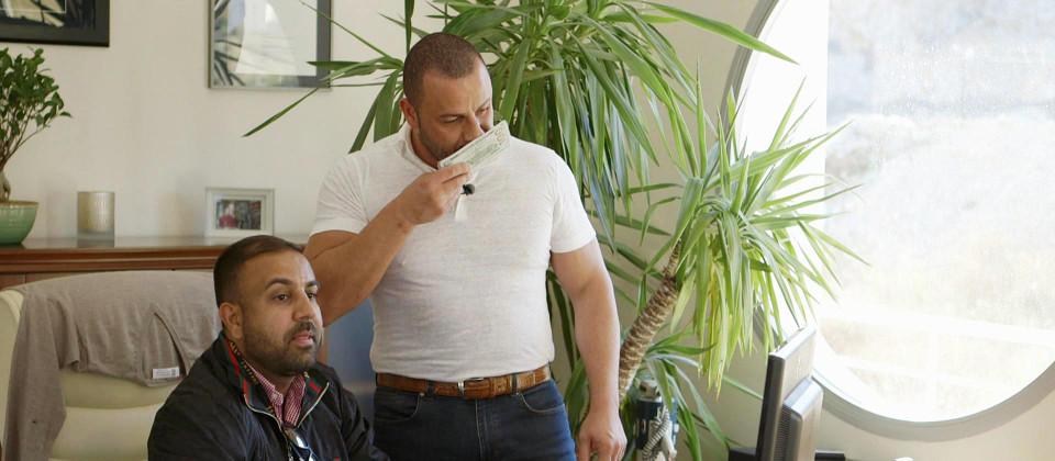 Versicherungsverkäufer Mehmet Göker riecht an einem Bündel Geldscheine.