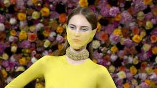 Ein Model mit transparentem Gesichtsschleier und gelbem Designkleid posiert vor einer Wand mit üppigem Blumendekor
