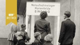 Familie vor Eingangsschild im Notaufnahmelager Marienfelde.