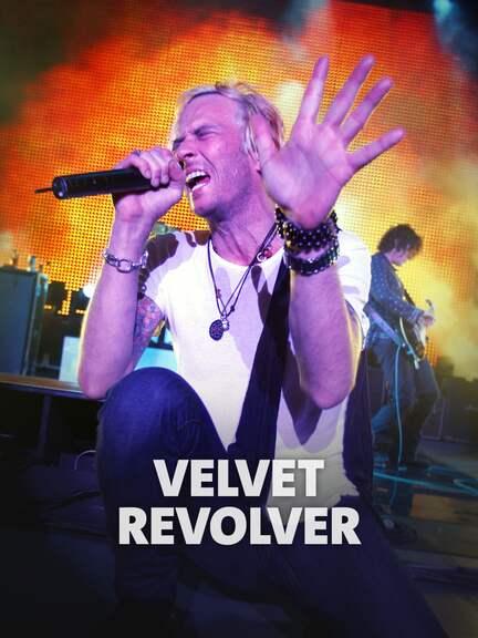 Der Frontmann der Band Velvet Revolver, Scott Weiland, kniet singend am vorderen Bühnenrand.