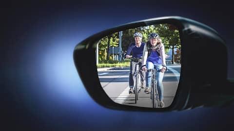 Zwei Fahrradfahrerinnen sind in einem Autorückspiegel zu sehen.