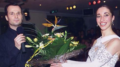 Eine Frau im Kleid hält einen Blumenstrauß, während ein Mann mit Mikro neben ihr steht.