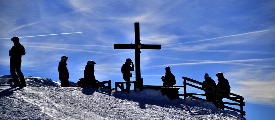 Ausflügler stehen am Gipfelkreuz und bewundern die Aussicht