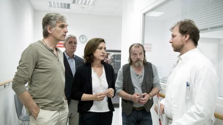 Eine Gruppe von Menschen spricht mit einem Arzt