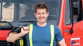 Ein mittelalter Mann steht vor einem Feuerwehrfahrzeug.