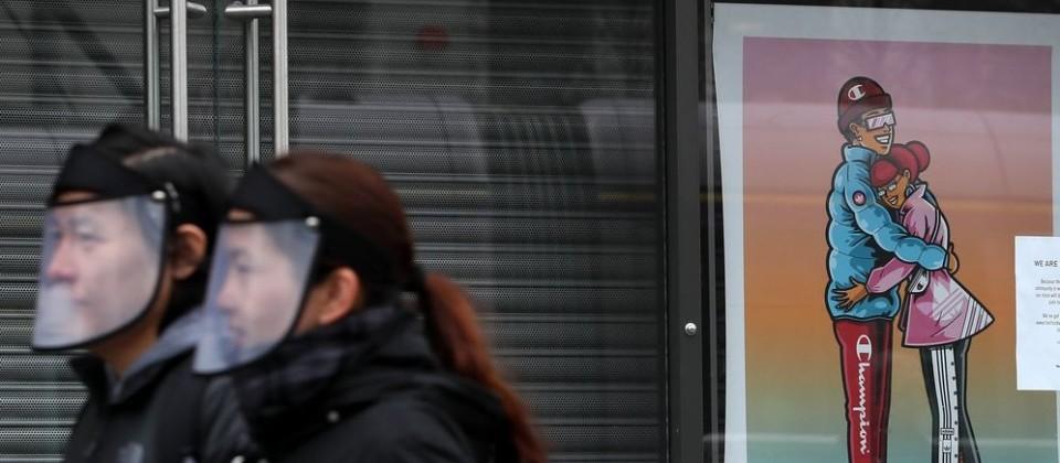 27.03.2020, Irland, Dublin: Ein Paar mit Gesichtsschutz-Visier gehen an einem Poster mit dem Titel «The Spirit of Love» (Der Geist der Liebe) des Künstlers Jawgem in einem Schaufenster in der O'Connell Straße vorbei. Foto: Brian Lawless/PA Wire/dpa +++ dpa-Bildfunk +++