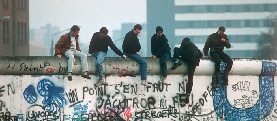 Sechs Männer sitzen auf der mit Graffiti bemalten Berliner Mauer.