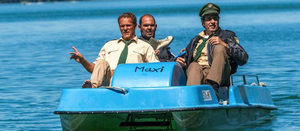 Hubert (Christian Tramitz, links) und Staller (Helmfried von Lüttichau, rechts) sitzen in einem Tretboot und fahren auf den See hinaus. Yazid (Hannes Ringelstetter) sitzt hinter ihnen in Tauchermontur.