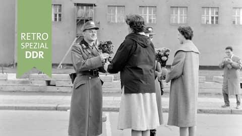 Frauen übergeben Blumen an DDR-Grenzschützer (1961)