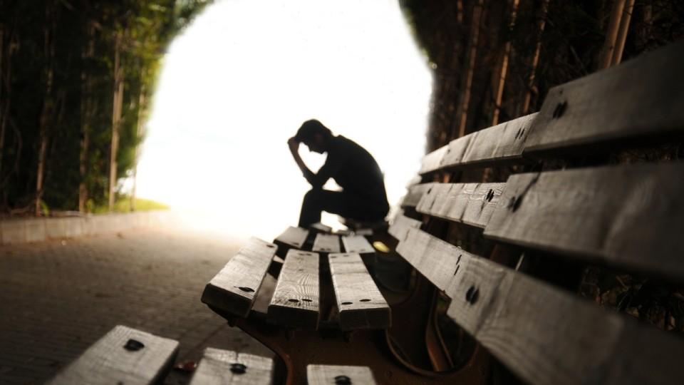 Depressiver Mann auf Parkbank
