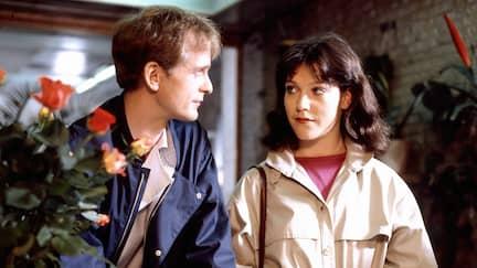 Eine junge Frau und ein junger Mann stehen an einem Tisch und schauen sich an, dabei unterschreibt der Mann etwas.