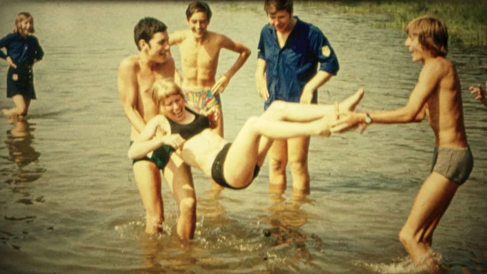 Ein paar Jugendliche spielen in einem See.