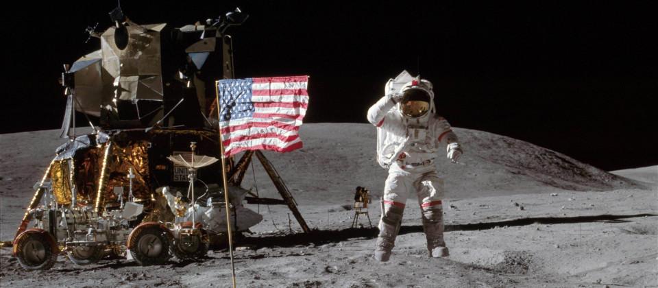 Der Astronaut Charles Duke salutiert im Raumanzug auf dem Mond neben der amerikanischen Flagge