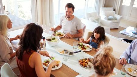 Familie sitzt am Tisch und isst.