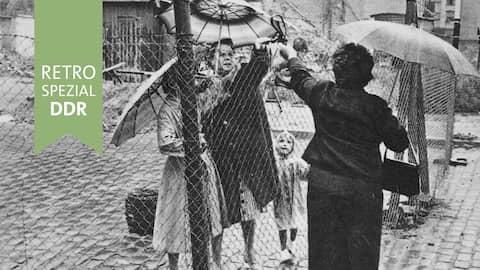 Frauen reichen Handtasche über Grenzzaun (1961)