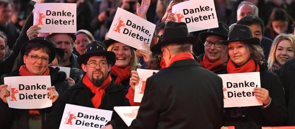 Berlinale: Abschluss und Verleihung der Bären im Berlinale Palast: Dieter Kosslick, Berlinale-Direktor, steht auf dem roten Teppich und hält ein Porträt von sich in der Hand. (Quelle: dpa/Jens Kalaene)