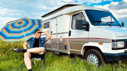 Reporter Friso Richter sitzt vor einem Camper.