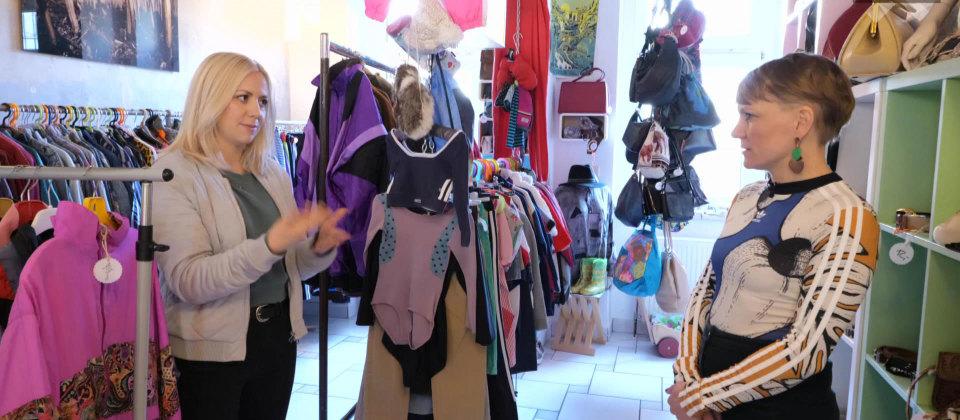Zwei Frauen stehen in einem Kleidungsgeschäft.