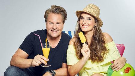Ein Mann und eine Frau im sommerlichen Outfit mit einem Drink und einem Eis.