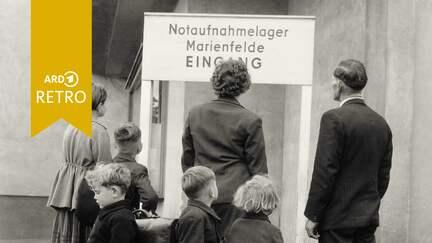 """Familie steht vor Schild """"Notaufnahmelager Marienfelde Eingang"""" (Quelle: rbb)"""