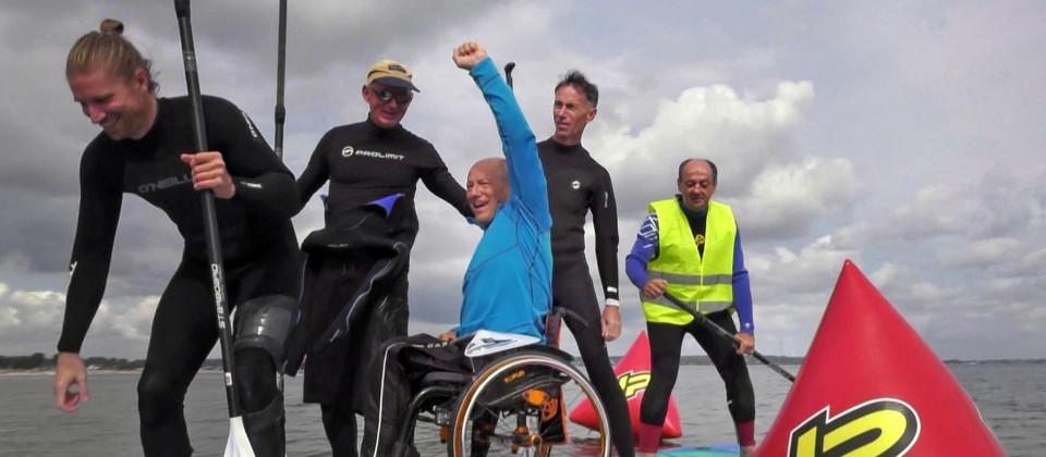 Ein großes Surfbrett auf dem Wasser mit fünf Männern, von denen einer im Rollstuhl sitzt und die Faust nach oben reckt.