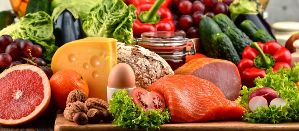 Ein Ensemble aus verschiedenen Obst- und Gemüsesorten, Nüssen, Fleisch, Fisch, Käse und Ei.