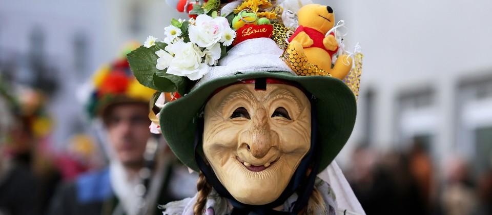 Maskierte mit Holzmaske beim traditionellen Fetzenzug in Ebensee