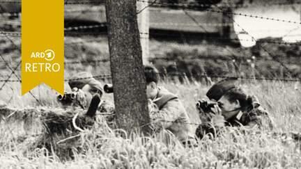Grenzsoldaten der DDR beobachten an der hessisch-thüringischen Grenze die westdeutsche Seite