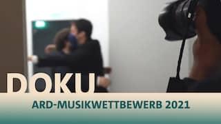 Das Geister Duo umarmt sich bei der Bekanntgabe des ersten Preises beim ARD-Musikwettbewerb  und eine Fotokamera hält den Moment fest.