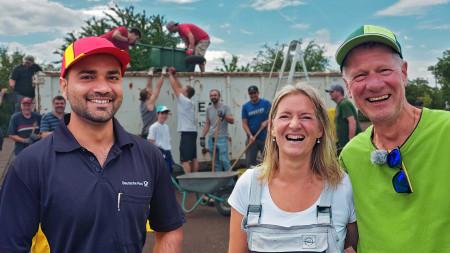 Zwei Männer und eine Frau lachen in die Kamera, während im Hintergrund mehrere Menschen gemeinsam an einem Container arbeiten.