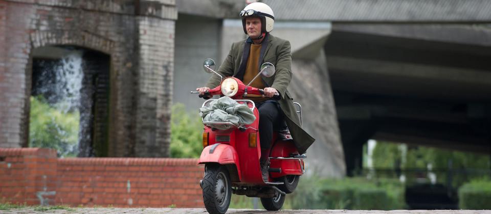 Kommissar Jürgen Stellbrink fährt auf seinem roten Roller