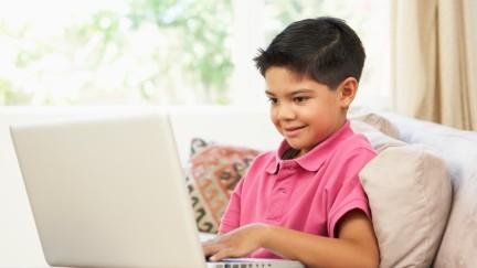 Mädchen sitzt vorm Laptop