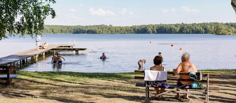 Menschen baden an einem See.
