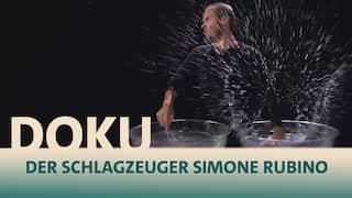 Schlagzeuger Simone Rubino schlägt mit einem Handrührer in mit Wasser gefüllte große Glasschüsseln und das Wasser spritzt dabei auf