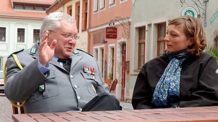 Ein älterer Mann sitzt an einem Tisch in einer Stadt.