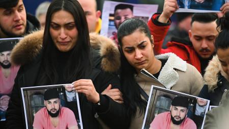 Menschen trauern in der Nähe des Tatortes Heumarkt und halten dabei Fotos der Opfer in den Händen.