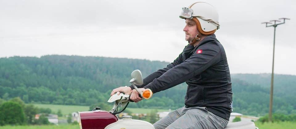 Ein Mann fährt auf einem alten Moped.