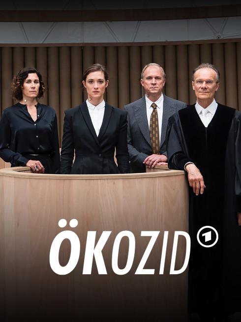 Vier Personen in einem Gerichtssaal. Alle sind adrett gekleidet.
