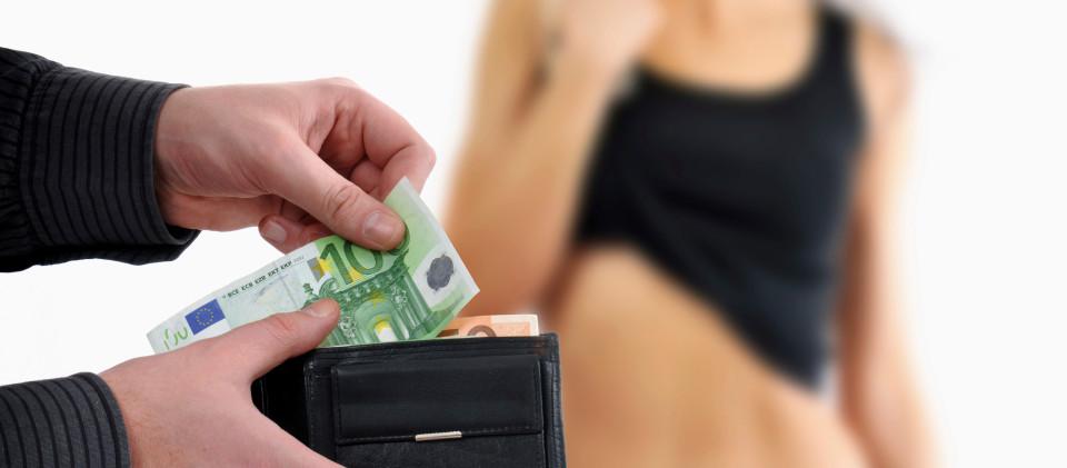 Vordergrund: Geldbörse aus der Hundert Euroscheine gezogen werden, Hintergrund: Nackte Frau in unscharfer Darstellung