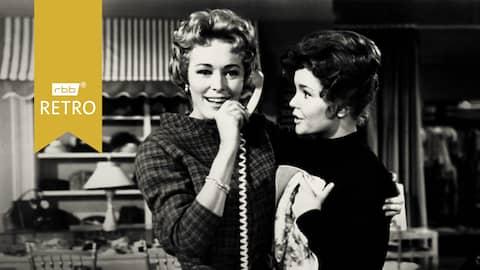 1961: Zwei Frauen halten sich im Arm, von denen eine telefoniert (Quelle: rbb/imago images/Everett Collection)